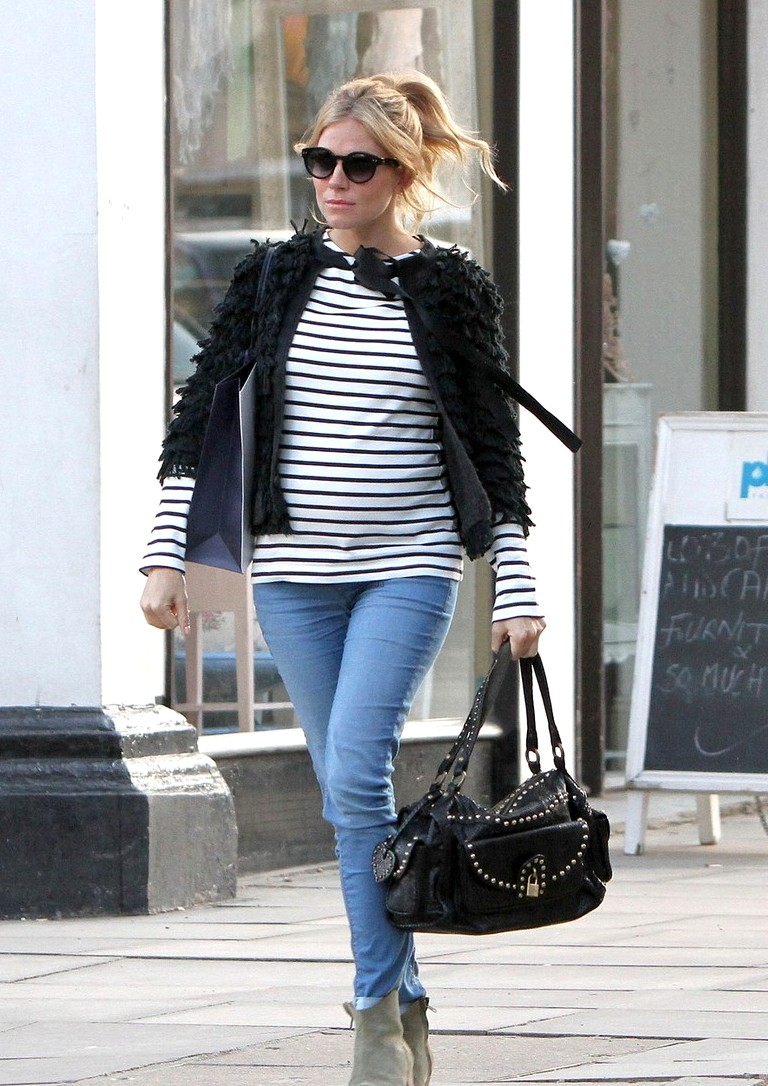 A heavily pregnant Sienna Miller shows off her growing baby bump while filming a commerical advert in Primrose Hill, London