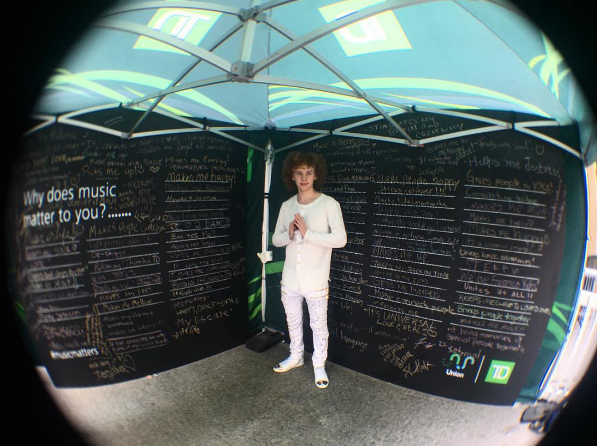 Francesco Yates posing with the Why Music Matters wall at the TD Union Block Party